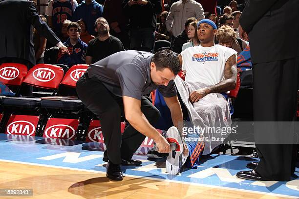 Carmelo Anthony of the New York Knicks gets tack put on his shoes prior to the game on January 3 2013 at Madison Square Garden in New York City NOTE...