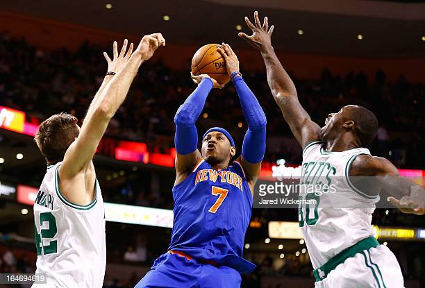 Carmelo Anthony of the New York Knicks goes up for a shot between two Boston Celtics defenders Shavlik Randolph and Brandon Bass during the game on...