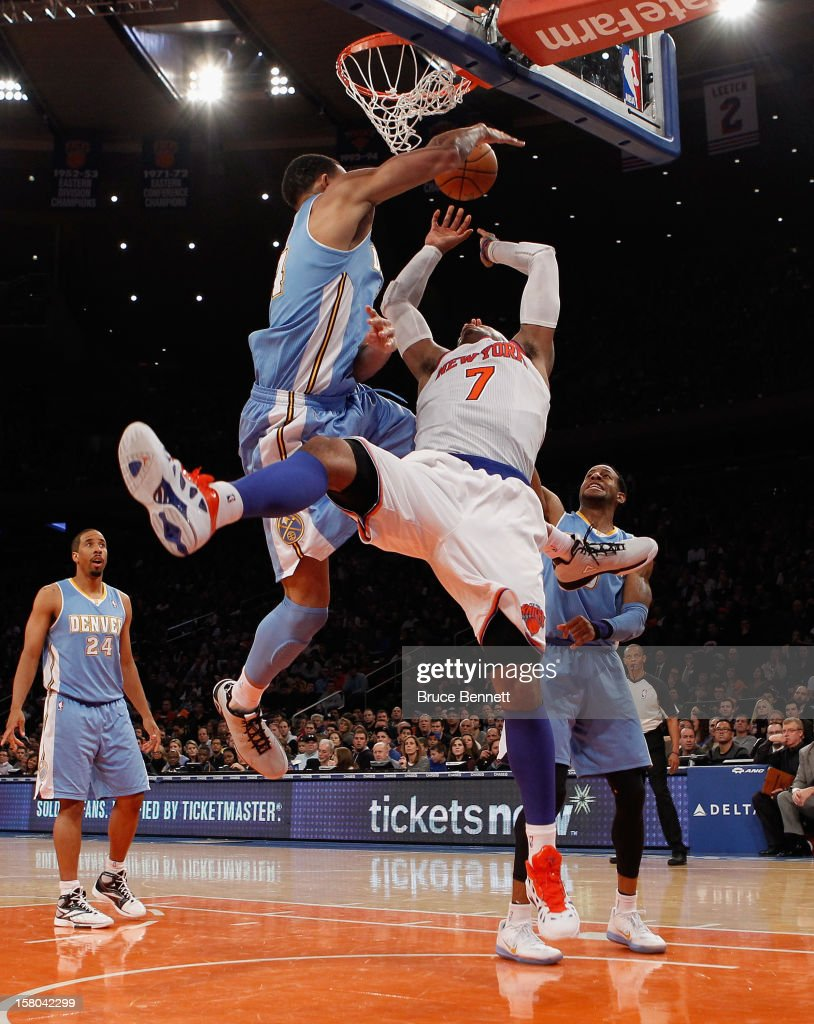 Carmelo Anthony #7 of the New York Knicks is blocked in his game against the Denver Nuggets at Madison Square Garden on December 9, 2012 in New York City.