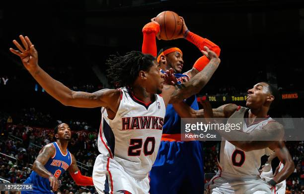 Carmelo Anthony of the New York Knicks is defended by Cartier Martin and Jeff Teague of the Atlanta Hawks at Philips Arena on November 13 2013 in...