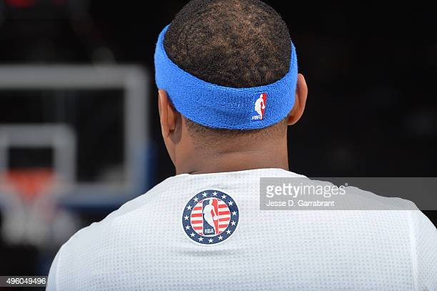 Carmelo Anthony of the New York Knicks looks on while wearing a warmup shirt with the NBA logo on it prior to the game against the Milwaukee Bucks at...