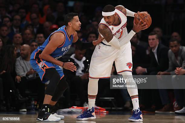 Carmelo Anthony of the New York Knicks looks to pass around Andre Roberson of the Oklahoma City Thunder during the second half at Madison Square...