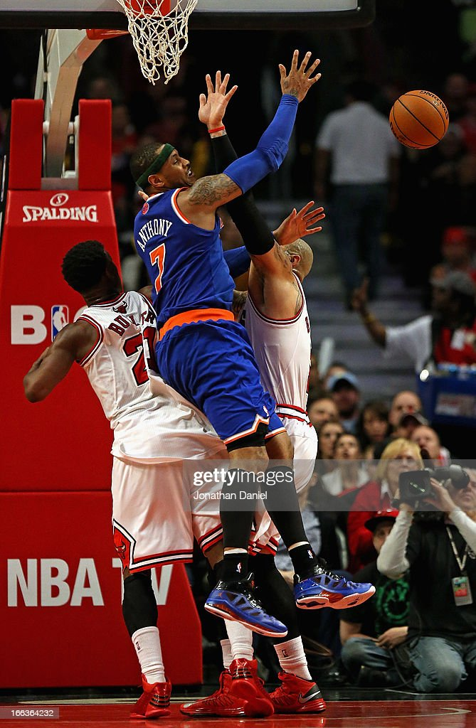 Carmelo Anthony #7 of the New York Knicks looses the ball under pressure from Jimmy Butler #21 (L) and Carlos Boozer #5 of the Chicago Bulls at the United Center on April 11, 2013 in Chicago, Illinois. The Bulls defeated the Knicks 118-111 in overtime.