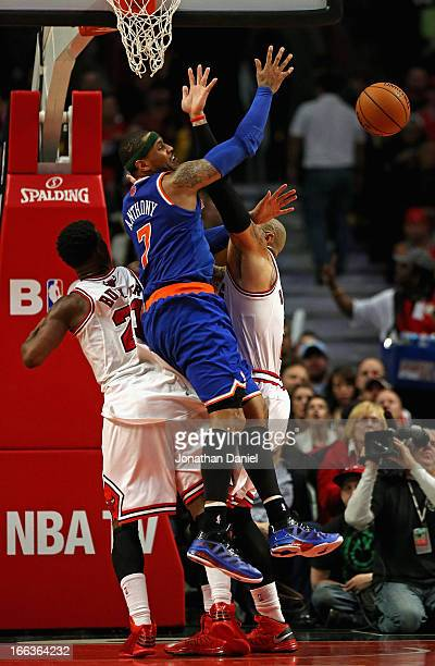 Carmelo Anthony of the New York Knicks looses the ball under pressure from Jimmy Butler and Carlos Boozer of the Chicago Bulls at the United Center...