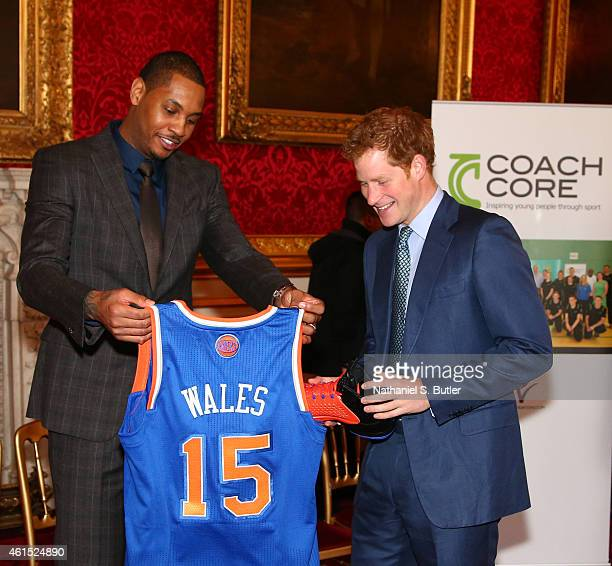 Carmelo Anthony of the New York Knicks presents a jersey and sneakers to Prince Harry at the Coach Core graduation ceremony. This event is part of...