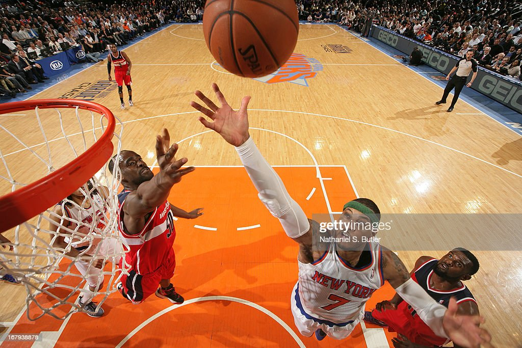 Carmelo Anthony #7 of the New York Knicks reaches for a rebound against Emeka Okafor #50 of the Washington Wizards on April 9, 2013 at Madison Square Garden in New York City.