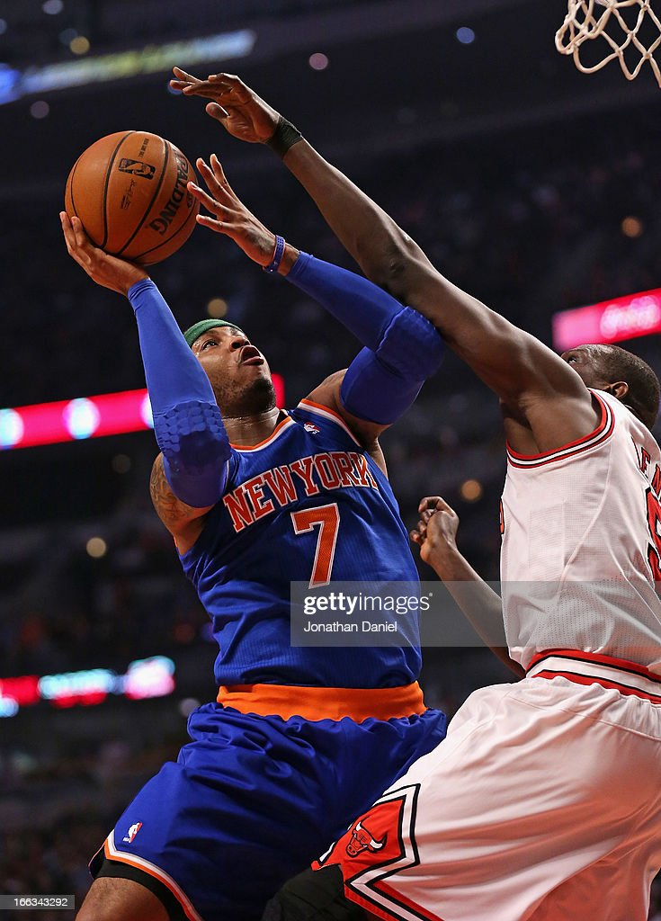 Carmelo Anthony #7 of the New York Knicks shoots against Loul Deng #9 of the Chicago Bulls at the United Center on April 11, 2013 in Chicago, Illinois.