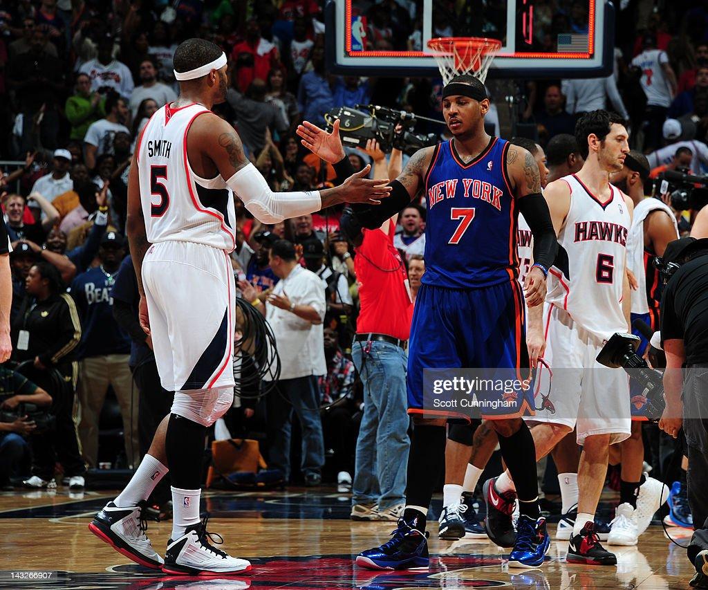 Carmelo Anthony #7 of the New York Knicks slaps hands with Josh Smith #5 of the Atlanta Hawks on April 22, 2012 at Philips Arena in Atlanta, Georgia.