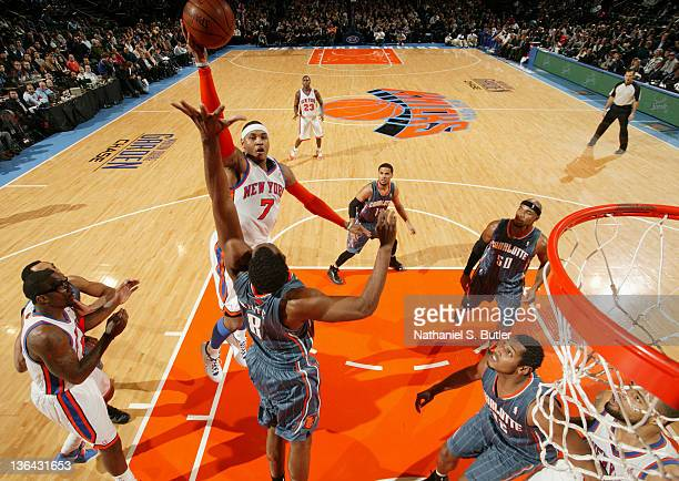 Carmelo Anthony of the New York Knicks takes a jump shot over DJ White of the Charlotte Bobcats during the game on January 4 2012 at Madison Square...