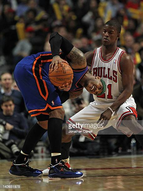 Carmelo Anthony of the New York Knicks tries to move against Jimmy Butler of the Chicago Bulls at the United Center on April 10 2012 in Chicago...