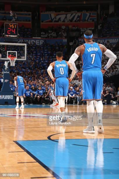 Carmelo Anthony of the Oklahoma City Thunder and Russell Westbrook of the Oklahoma City Thunder look on as Paul George of the Oklahoma City Thunder...
