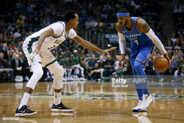 Carmelo Anthony of the Oklahoma City Thunder dribbles the ball while being guarded by John Henson of the Milwaukee Bucks in the second quarter at the...