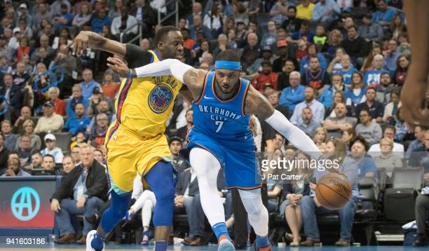 Carmelo Anthony of the Oklahoma City Thunder drives around Draymond Green of the Golden State Warriors during the first half of a NBA game at the...
