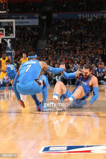 Carmelo Anthony of the Oklahoma City Thunder helps Steven Adams to his feet during the game against the Los Angeles Lakers on January 17 2018 at...