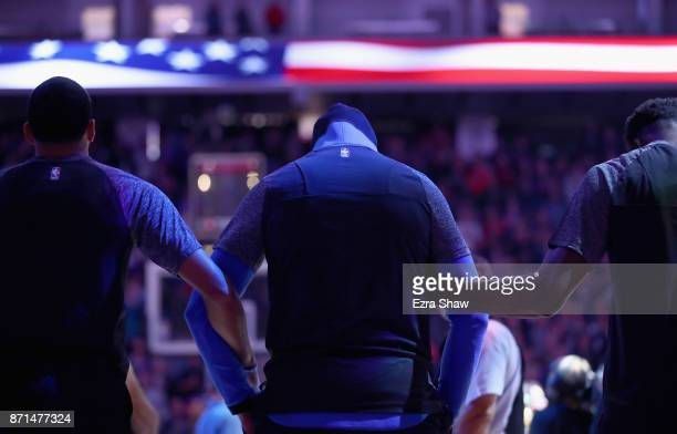 Carmelo Anthony of the Oklahoma City Thunder locks arms with teammates during the playing of the National Anthem before their game against the...