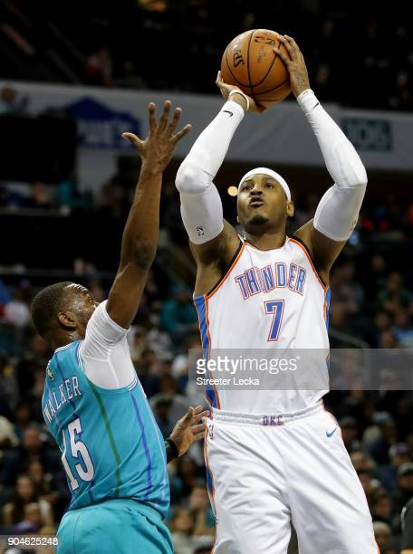 Carmelo Anthony of the Oklahoma City Thunder shoots over Kemba Walker of the Charlotte Hornets during their game at Spectrum Center on January 13...