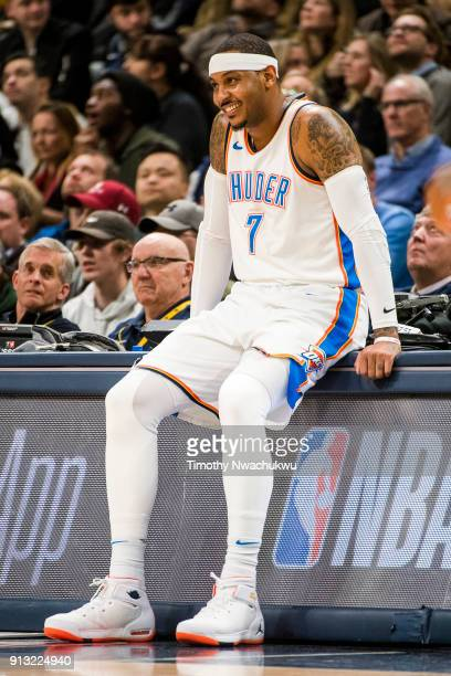 Carmelo Anthony of the Oklahoma City Thunder smiles from the scorer's table during action against the Denver Nuggets at Pepsi Center on February 1...