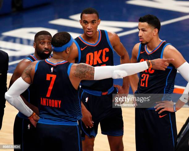 Carmelo Anthony of the Oklahoma City Thunder talks with teammates Raymond Felton Terrance Ferguson and Andre Roberson during a timeout in an NBA...