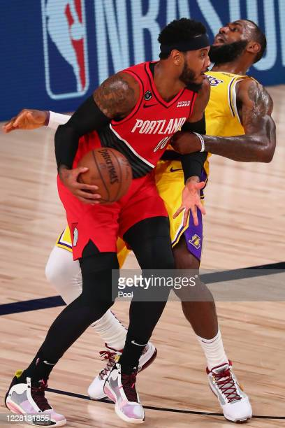 Carmelo Anthony of the Portland Trail Blazers commits an offensive foul against LeBron James of the Los Angeles Lakers during the second half in game...