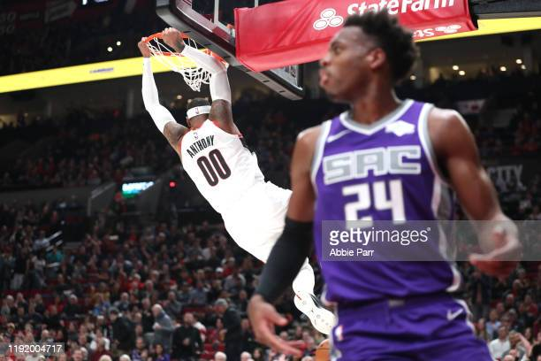 Carmelo Anthony of the Portland Trail Blazers dunks the ball alongside Buddy Hield of the Sacramento Kings in the first quarter during their game at...