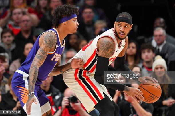 Carmelo Anthony of the Portland Trail Blazers right handles the ball against Kelly Oubre Jr #3 of the Phoenix Suns during the first half of the game...