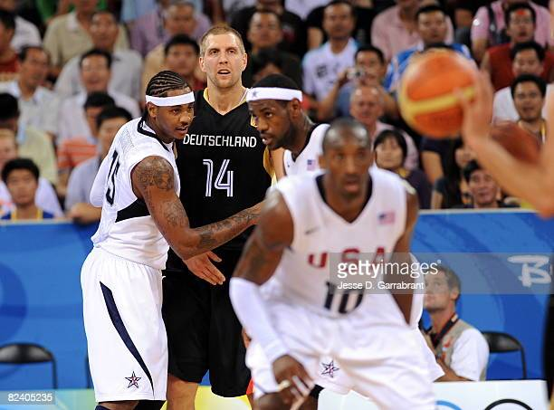 Carmelo Anthony of the U.S. Men's Senior National Team defends against Dirk Nowitzki of Germany during the men's group B basketball preliminaries at...