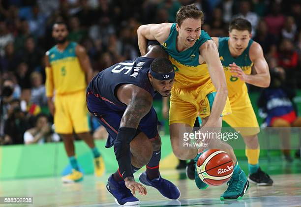 Carmelo Anthony of United States goes for the loose ball against Cameron Bairstow and Matthew Dellavedova of Australia during the Men's Preliminary...