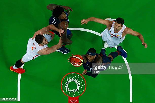 Carmelo Anthony of United States goes to the basket against Pau Gasol and Felipe Reyes of Spain as DeAndre Jordan of United States looks on during...