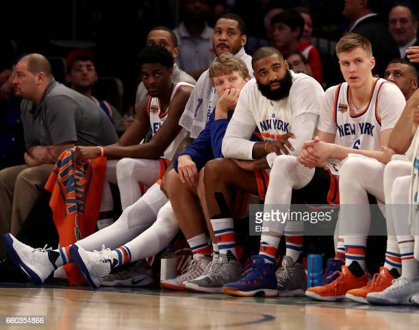 Carmelo AnthonyMindaugas KuzminskasKyle O'Quinn and Kristaps Porzingis of the New York Knicks look on from the bench in the fourth quarter against...