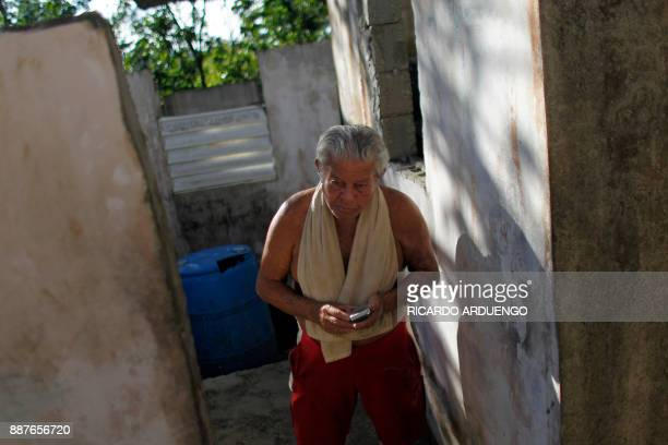 Carmelo Lopez Rivera walks inside his house damaged by Hurricane Maria in Vieques Puerto Rico on November 26 2017 / AFP PHOTO / Ricardo ARDUENGO / TO...