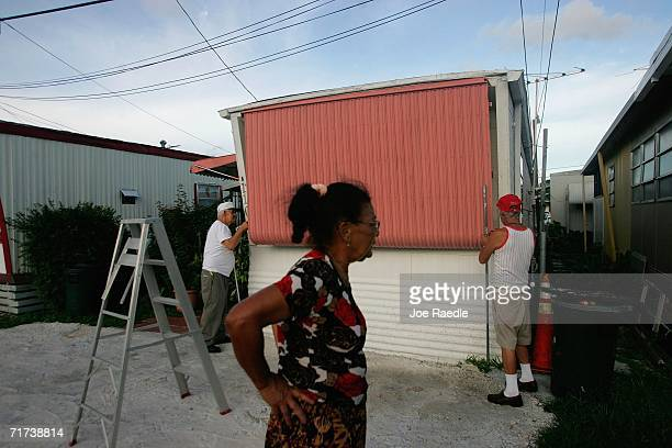 Carmen Acosta watches as Louis Chedebeau and Jose Planca put a shutter over their mobile home's window as they prepare for the approaching Tropical...