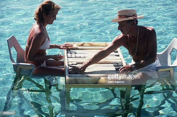 Carmen Alvarez enjoying a game of backgammon with Frank 'Brandy' Brandstetter in a swimming pool at Acapulco.
