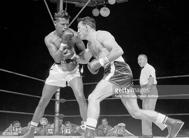 Carmen Basilio rips right hand at Ray Robinson in first round of middleweight bout at Yankee Stadium