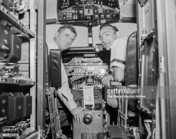 Carmen Basilio sitting with the pilot in the cockpit of a Mohawk Airlines airplane in Watertown New York August 20 1957