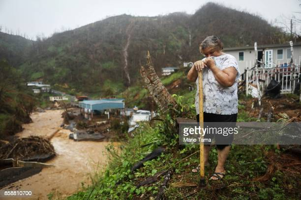 Carmen Cintron Torres takes a break from cleaning debris in front of her home more than two weeks after Hurricane Maria hit the island on October 7...