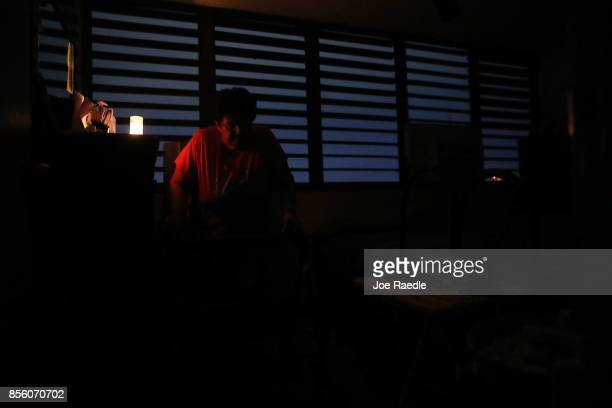 Carmen Correa uses a candle for light in her dark apartment as she and other residents of the 62 and over Moradas Las Teresas's Uno and Dos condo...