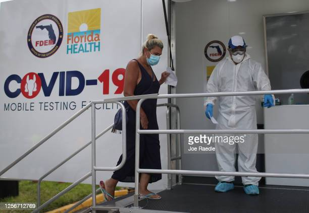 Carmen Garcia prepares to have her nose swabbed by a nurse through a glass pane in the Aardvark Mobile Health's Mobile Covid-19 Testing Truck on July...
