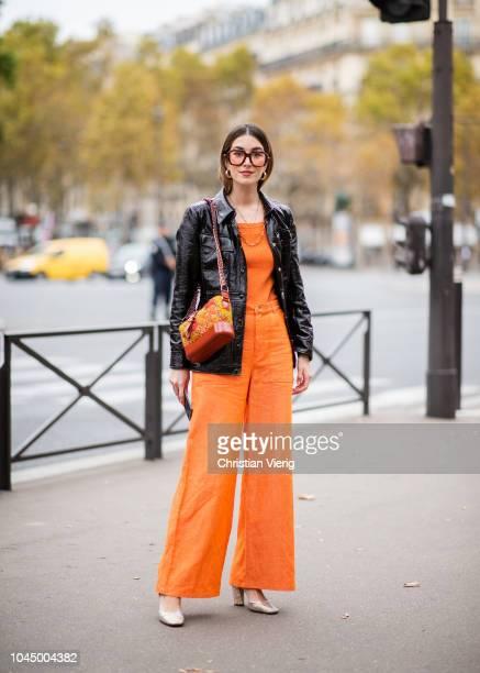 Carmen Hamilton wearing orange wide leg pants black vinyl jacket is seen outside Miu Miu during Paris Fashion Week Womenswear Spring/Summer 2019 on...
