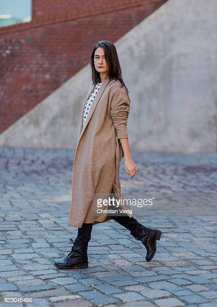 Carmen Launspach wearing a beige wool coat SET wearing white sweater with black print from Munthe black denim jeans Mango black heavy boots Jonak...
