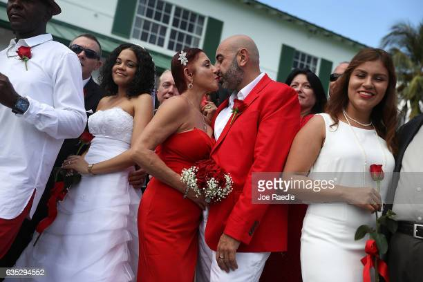 Carmen Lombardo and Armando Merola kiss as they participate in a group Valentine's day wedding at the National Croquet Center on February 14 2017 in...