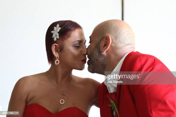Carmen Lombardo and Armando Merola kiss as they wait to be wed during a group Valentine's day wedding ceremony at the National Croquet Center on...