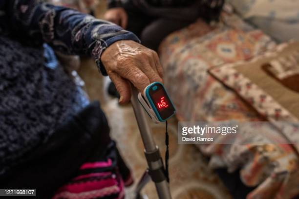 Carmen Maya is checked her oxygen level using a oximeter during a domiciliary visit on April 28, 2020 in Les Roquetes del Garraf, near Barcelona,...