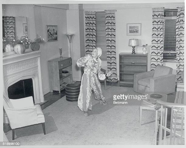 Carmen Miranda American singer shown in her living room dressed in one of her usual flamboyant outfits