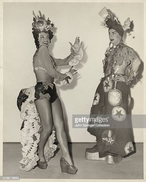 Carmen Miranda dances playfully in front of costume designer and actor Sascha Brastoff Brastoff is dressed in a makeshift costume resembling one of...