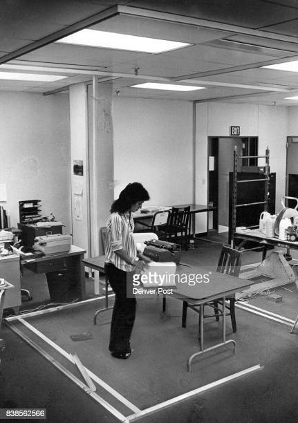 Carmen Miranda Receptionist Looks Up Data Strips on floor delineate partitions for interview room Credit Denver Post Inc
