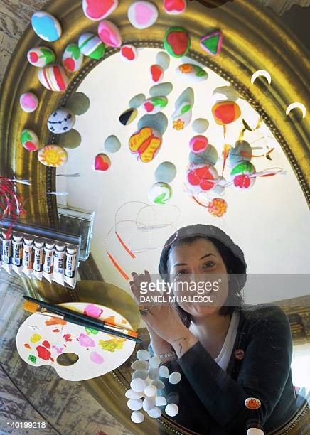 Carmen Miron a 23 yearold Romanian girl poses next to her martisor creations in Bucharest on February 24 2012 Every March 1st parents and children...