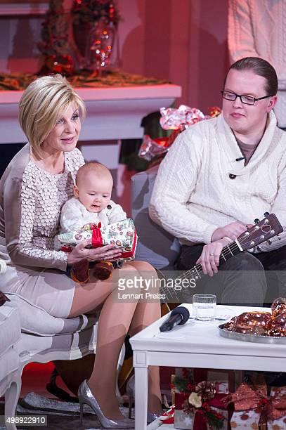 Carmen Nebel holds four months old William son of Angelo Kelly during the 'Heiligabend mit Carmen Nebel' TV show at Bavaria Filmstudios on November...