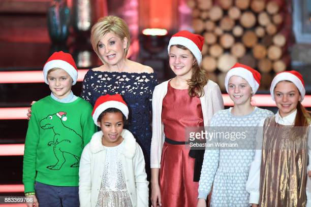 Carmen Nebel performs with children during the tv show 'Heiligabend mit Carmen Nebel' on November 29 2017 in Munich Germany The show will be aired on...