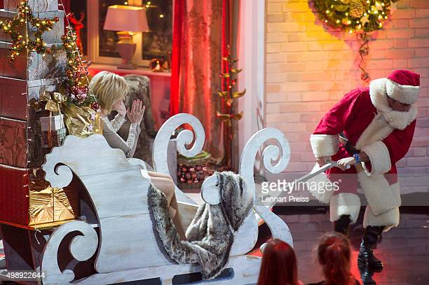 Carmen Nebel sits on a sledge pulled by Andy Borg as Santa Borg during the recording of the 'Heiligabend mit Carmen Nebel' TV show at Bavaria...