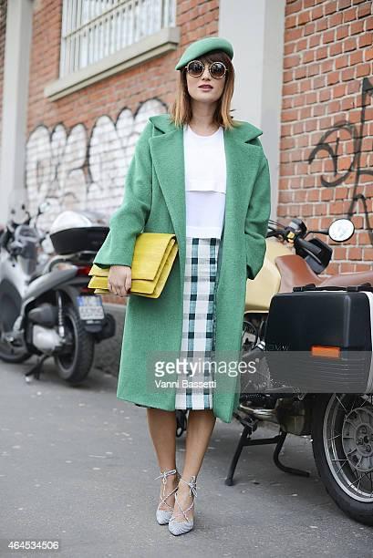 Carmen Negoita poses wearing Urban Post coat Other Stories top Zara skirt Ana Parvan X Carmen Negoita shoes Ralph Laurent hat and Yvy Bags bag on...